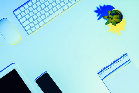 blue toned picture of plant, computer mouse and keyboard, digital tablet, smartphone, pen and textbook  Stock Photo