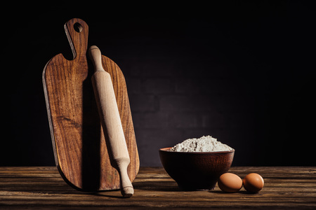 closeup view of wooden cutting board, rolling pin, bowl with flour and two eggs on table