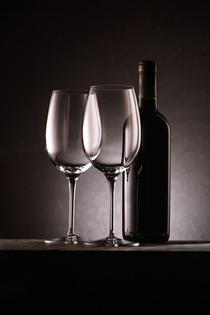 bottle of wine with two empty glasses on black