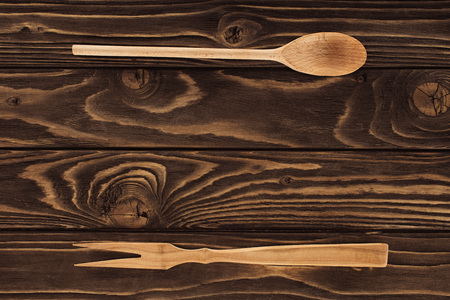 elevated view of wooden fork for meat and spoon on table  Stockfoto