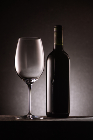 bottle of wine with empty glass on black Banco de Imagens