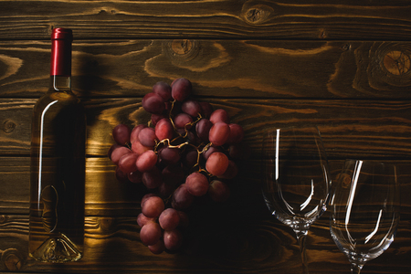 top view of bottle of white wine with grapes and glasses on wooden table Stock Photo
