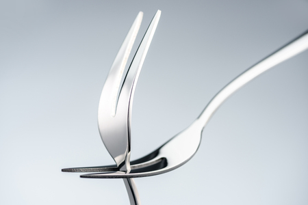 shiny forks with two tines isolated on grey