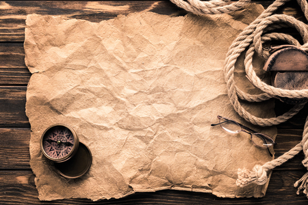 top view of blank crumpled paper with compass and rope on rustic wooden surface Banco de Imagens