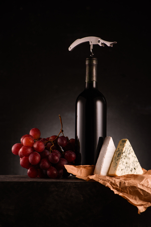 bottle of red wine pierced with corkscrew and grapes with cheese on table Stock Photo