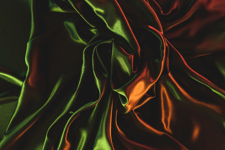 close up view of dark green crumpled silk cloth as backdrop