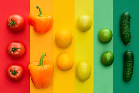 top view of ripe bell peppers, oranges and limes on colored surface Stock Photo