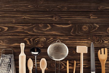 elevated view of kitchen utensils placed in row on wooden table Stockfoto