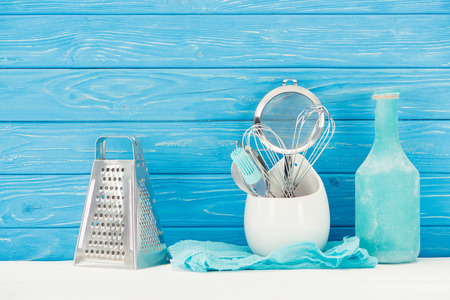 closeup view of rag, bottle, pastry brush, grater, whisks and sieve in front of blue wooden wall 스톡 콘텐츠