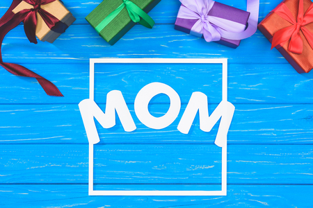 top view of gift boxes and word mom in frame on blue table, mothers day concept Stock Photo