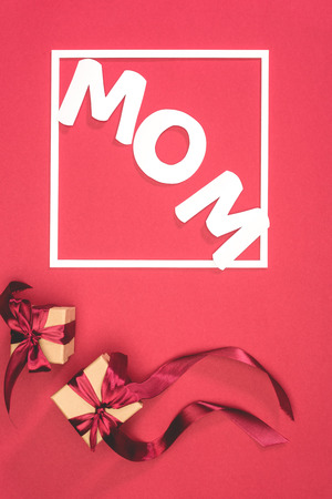 top view of gift boxes and word mom in frame on red surface, mothers day concept
