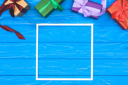 top view of gift boxes and blank frame on blue table Stock Photo