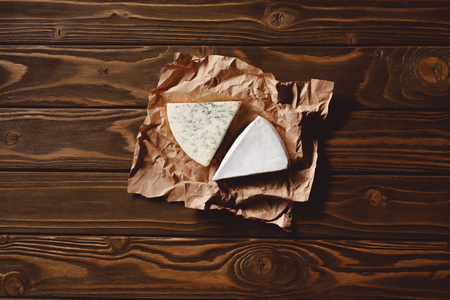 top view of slices of cheese on crumpled paper on wooden table