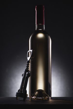 close-up shot of bottle of white wine with corkscrew on black