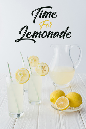 close up view of time for lemonade lettering, lemonade in glasses and jug on wooden tabletop on grey backdrop Stockfoto