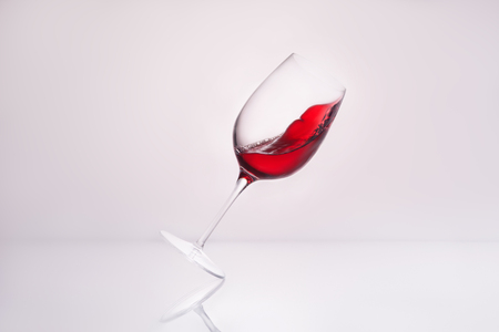 close-up shot of inclined wineglass with splashing red wine on reflective surface and on white