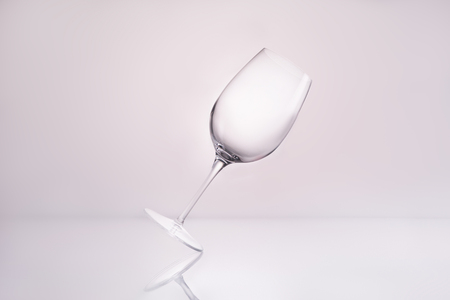 empty inclined wineglass on reflective surface and on white
