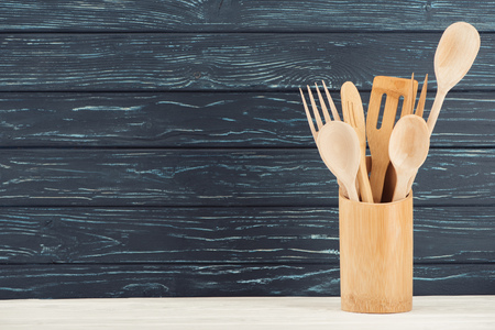 closeup view of kitchen utensils in front of wooden wall