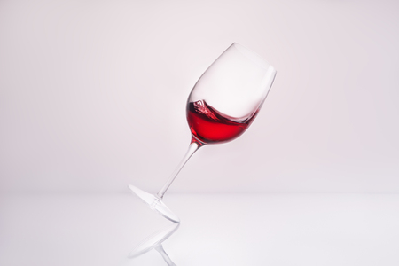inclined wineglass with delicious red wine on reflective surface and on white Stock Photo