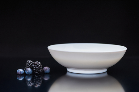 Blackberries and blueberries by white bowl on black background