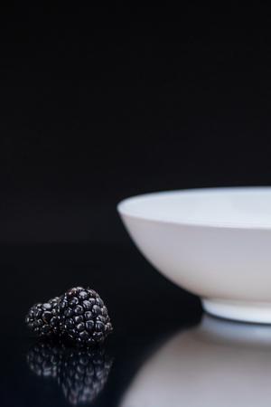 Ripe blackberries by white bowl on black background