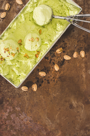 elevated view of pistachio ice cream with scoop and pistachios on table Archivio Fotografico - 101316643