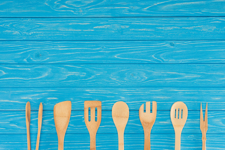 top view of wooden kitchen utensils placed in row on blue table