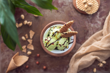 top view of yummy pistachio ice cream with waffles in glass on table Imagens
