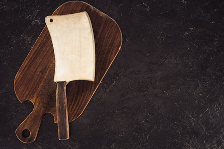 top view of butcher axe on wooden cutting board on marble table
