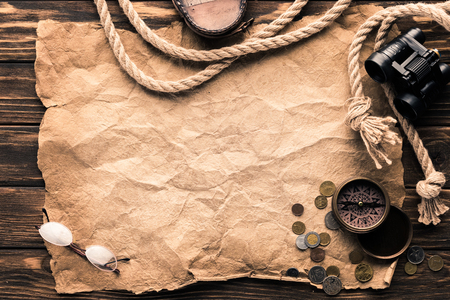 top view of blank crumpled paper with compass, binoculars and rope on rustic wooden surface Stock Photo - 101317998