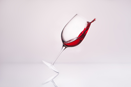 inclined wineglass with luxury red wine on reflective surface and on white