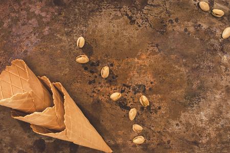 top view of empty ice cream cones and pistachios on table Archivio Fotografico - 101318443