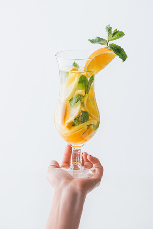 cropped shot of woman holding fresh cocktail with mint and citrus fruits isolated on white Stock fotó