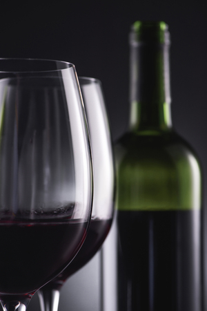 close-up shot of glasses filled with red wine and wine bottle blurred on background