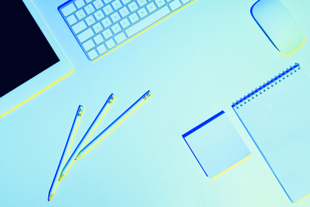 blue toned picture of pencils, digital tablet, computer keyboard and mouse, textbook and sticky note  Stock Photo