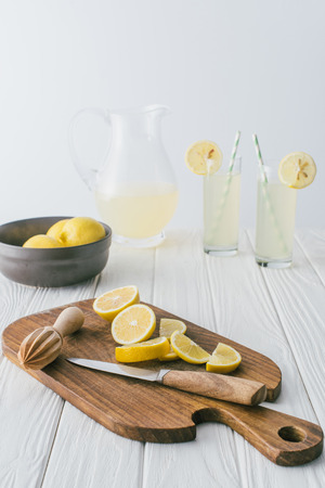 close up view of lemons, knife, wooden pestle on cutting board and lemonade in glasses on white wooden tabletop on grey backdrop