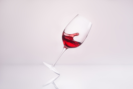 inclined wineglass with splashing delicious red wine on reflective surface and on white