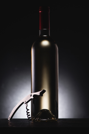 close-up shot of bottle of delicious white wine on black with corkscrew