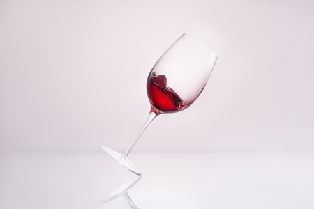 inclined glass with red wine on reflective surface and on white