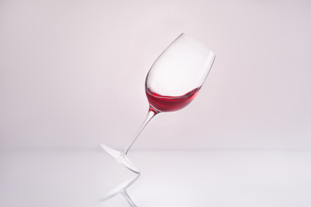 inclined wineglass with splashing luxury red wine on reflective surface and on white