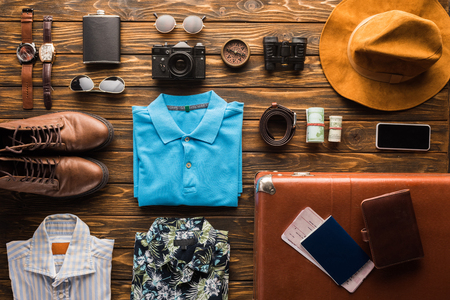 top view of vintage suitcase with baggage for travel on wooden surface Stock Photo