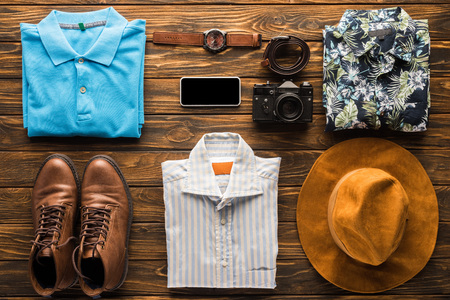 top view of stylish clothes with film camera and smartphone on wooden surface, travel concept