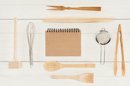 top view of textbook and kitchen utensils on wooden white table   스톡 콘텐츠