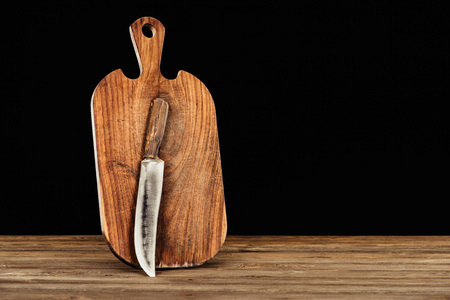 closeup view of knife and wooden cutting board on black background  스톡 콘텐츠