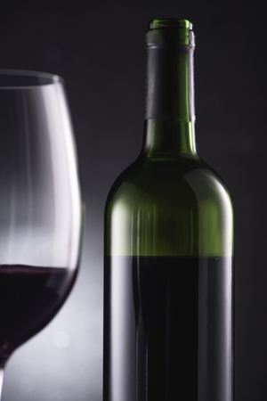 close-up shot of blurred glass filled with red wine on foreground and wine bottle on black