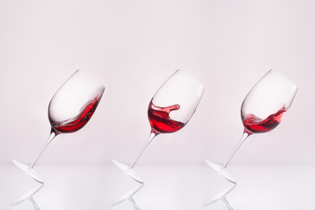 row of inclined wineglasses with splashing wine on reflective surface and on white