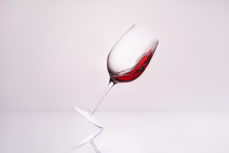 inclined wineglass with red wine on reflective surface and on white