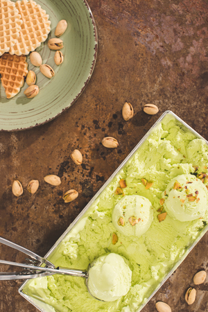 top view of green pistachio ice cream with scoop on table