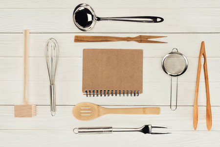 elevated view of textbook and kitchen utensils on wooden white table  스톡 콘텐츠