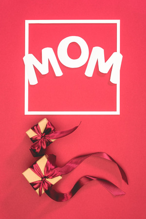 top view of gift boxes with ribbons and word mom in frame on red surface, mothers day concept Stock Photo